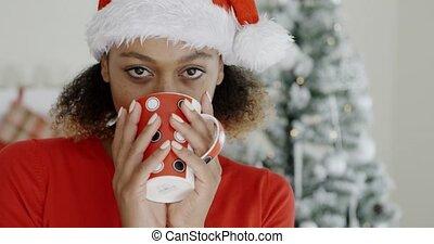 Young woman enjoying hot coffee at Christmas