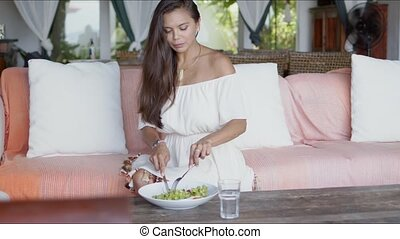 Young woman enjoying lunch at home sofa - Pretty smiling ...