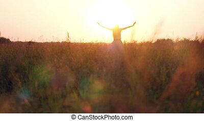 Young woman enjoying nature and sunlight in straw field....