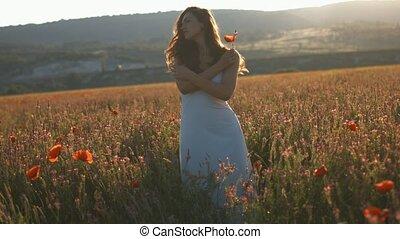 Young woman enjoying nature .Young beautiful woman walking among blooming poppy flowers