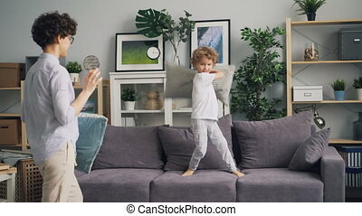 Young woman enjoying pillow fight with small child throwing...