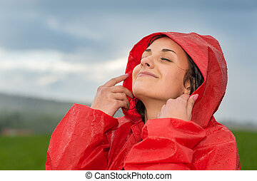 Young woman enjoying raindrops on her face