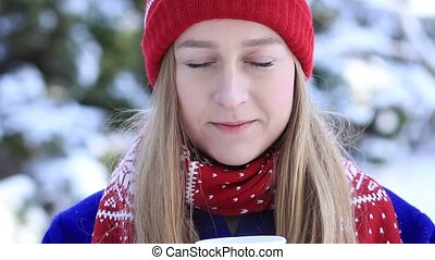 Young woman enjoying scent of coffee in wintertime -...