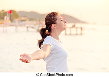 young woman enjoying the freedom with open arms