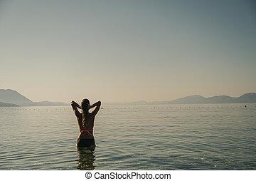 Young woman enjoying the morning sea