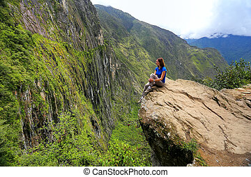 Young woman enjoying the view of Inca Bridge and cliff path ...