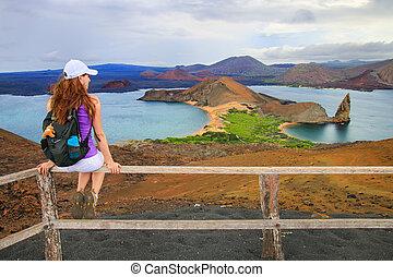 Young woman enjoying the view of Pinnacle Rock on Bartolome island, Galapagos National Park, Ecuador.