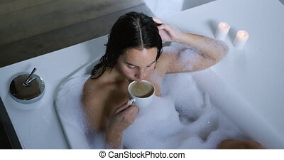 High angle view of a young Caucasian woman with long dark hair relaxing in a foam bath with lit candles beside the bath, drinking a cup of coffee, slow motion