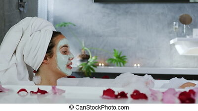 Side view of a young Caucasian woman in a modern bathroom with a face pack on and her hair wrapped in a towel, relaxing in a foam bath with rose petals around it and lit candles in the background, having fun blowing the bubbles, slow motion