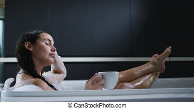 Side view of a young Caucasian woman with long dark hair relaxing in a foam bath with eyes closed and her feet up, holding a cup of coffee, with lit candles beside the bath, slow motion