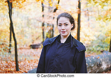young woman enjoying walk through forest in autumn