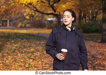 young woman enjoying walk through park in autumn