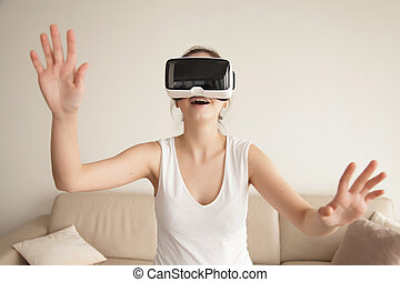 Young woman enjoys VR gaming on sofa at home