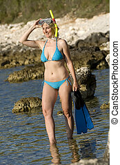 fins - young woman entering water with snorkle and fins