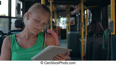 Young woman entertaining with pad during bus ride