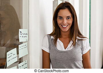 Young woman entrepreneur in her startup office smiling