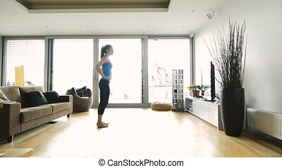 Young woman exercising at home, doing lunges.