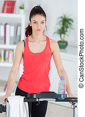 young woman exercising at home on stepper trainer