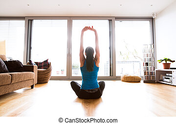 Young woman exercising at home, stretching arms. - Beautiful...