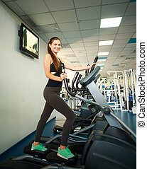 Young woman exercising on cardio machines in gym