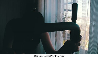 Young Woman Exercising on Elliptical Machine at Home on Against the Window