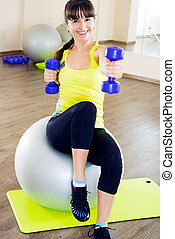 Young cheerful smiling woman exercising with dumbbells and fitball