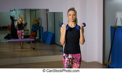 Young woman exercising with dumbbells at the gym looking at camera