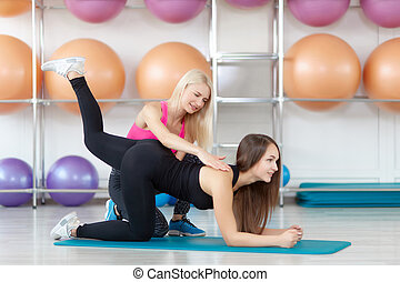 Young woman exercising with her fitness instructor