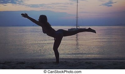 Young woman exercising yoga, doing pose on beach during...