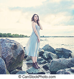 Young woman fashion model in gray dress outdoors