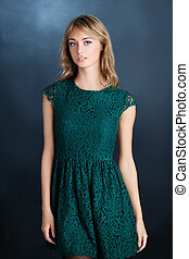Young woman fashion model wearing green dress, portrait
