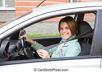 Young woman fastening in car
