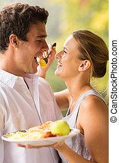 young woman feeding boyfriend breakfast