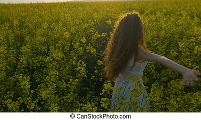 Young woman feeling happy and spinning in canola field enjoying nature