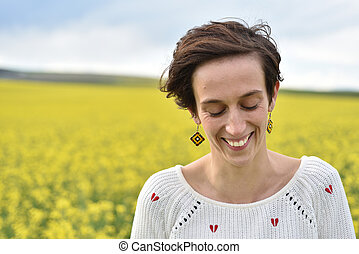 Young woman feeling happy in the middle of a canola field