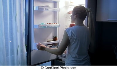Young woman feeling hungry at night opens refrigerator
