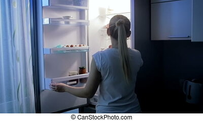 Young woman feeling hungry at night takes yoghurt from...