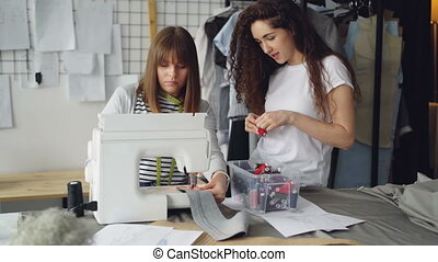 Young woman female designer is working with sewing machine while her partner is looking at stitches and choosing threads from box. Informal friendly atmosphere.
