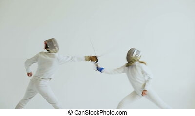 Young woman fencer having fencing training with trainer in...
