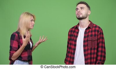 Young woman fighting young man against green background -...