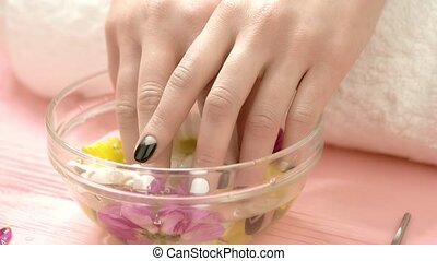 Young woman fingers in aroma bath. Female beautiful hands...
