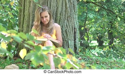 young woman finished reading book under thick tree trunk. 4K