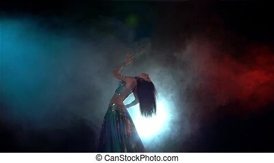 Young woman finishing belly dance in blue dress with long dark hair , back light, red, blue, smoke, slow motion