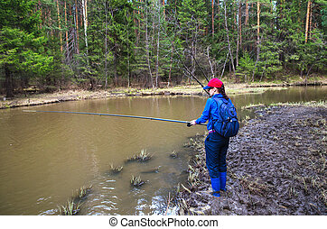 Young woman fishing on a small river