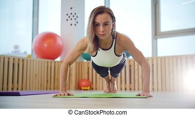 Young woman fitness trainer doing push ups in the bright studio