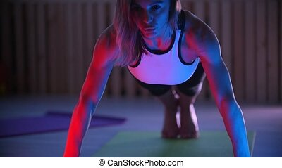 Young woman fitness trainer doing push ups in the studio in neon lighting