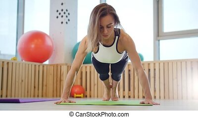 Young woman fitness trainer doing push ups in the studio