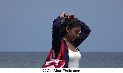Young Woman Fixing Hair Near Ocean