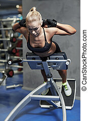 young woman flexing back muscles on bench in gym