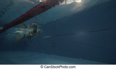 Young woman floating breaststroke in swimming waterpool...